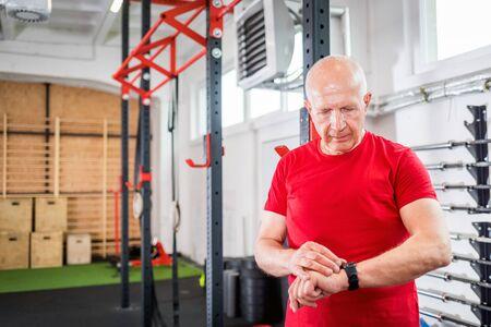 Senior man at the gym using smartwatch Reklamní fotografie