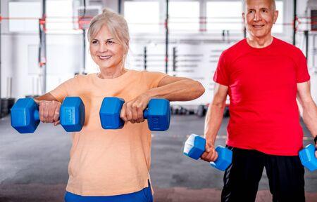 Senior people with dumbbells doing exercises at the gym Reklamní fotografie - 127358305