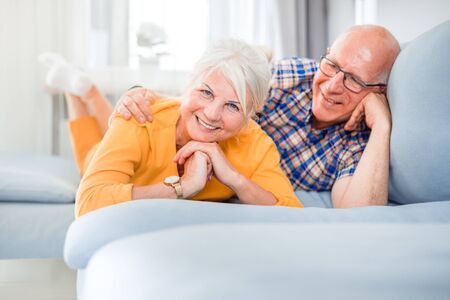 Portrait of cheerful senior couple relaxing and lying on sofa at home Reklamní fotografie - 127358306