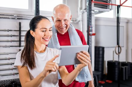 Personal trainer showing results of training on tablet to senior man at the gym Reklamní fotografie - 127358314