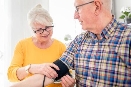 Senior wife doing blood pressure measurement at home to her husband Reklamní fotografie - 127358315