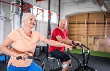 Senior couple biking at the gym Reklamní fotografie