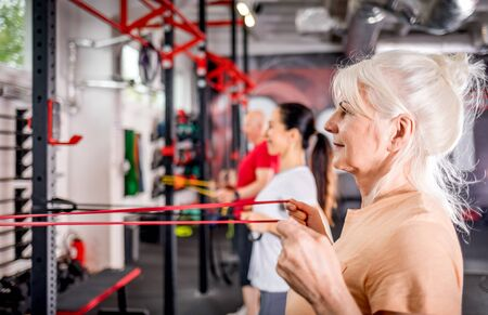 Senior people with trainer using resistance band doing exercises at the gym Reklamní fotografie - 127358363