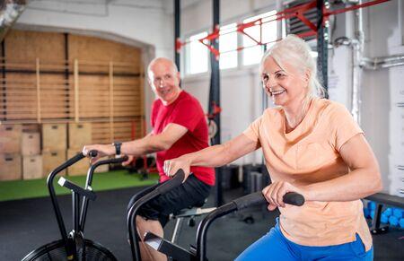 Senior couple biking at the gym Reklamní fotografie - 127358368