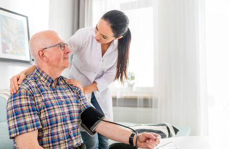 Nurse visiting senior male at home doing blood pressure measurement Reklamní fotografie - 127358371