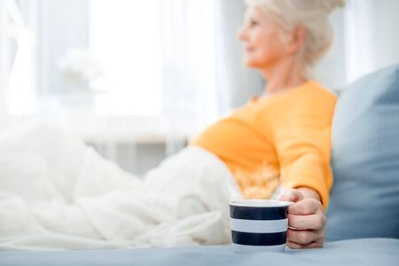 Senior woman at home relaxing on sofa with blanket holding cup of coffee Reklamní fotografie - 127358373