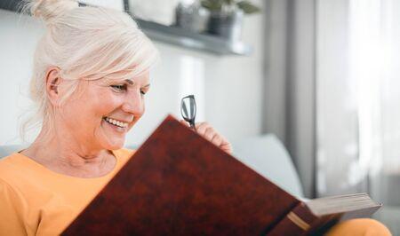 Cheerful senior female holding family photo album sitting on sofa at home