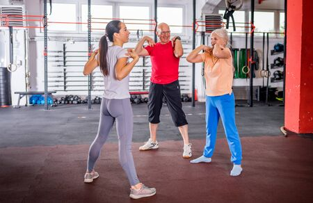 Senior people workout with personal trainer in rehabilitation center