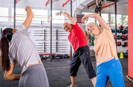Senior people workout with personal trainer in rehabilitation center Reklamní fotografie - 127358393