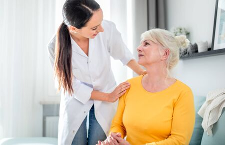 Smiling nurse talking with senior female during home visit