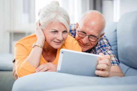 Happy senior couple looking at tablet lying on sofa at home