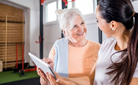 Trainer working with senior woman at the gym using tablet Reklamní fotografie - 127358675