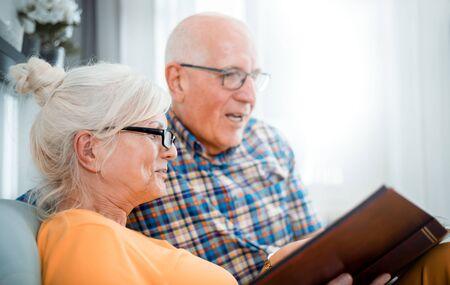 Cheerful senior couple holding family photo album sitting on sofa at home Reklamní fotografie