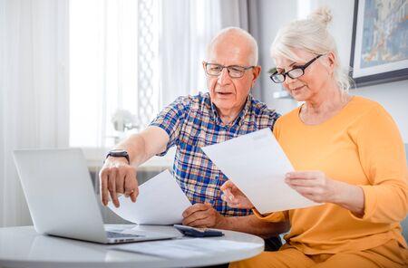 Senior couple checking bills using laptop at home Reklamní fotografie - 127358720