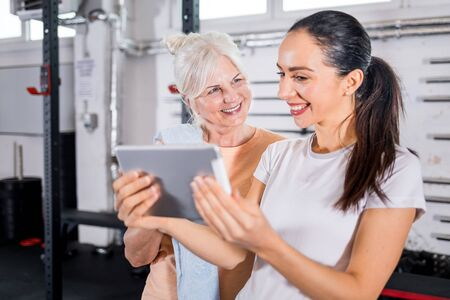 Trainer working with senior woman at the gym using tablet