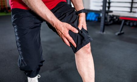 Senior man at the gym suffering from pain in knee