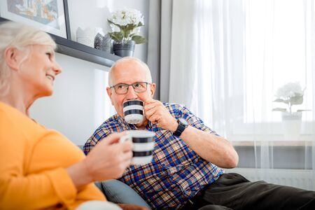 Senior couple at home spending time together drinking tea or coffee Reklamní fotografie - 127359210