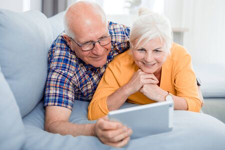 Happy senior couple looking at tablet lying on sofa at home Reklamní fotografie - 127359203