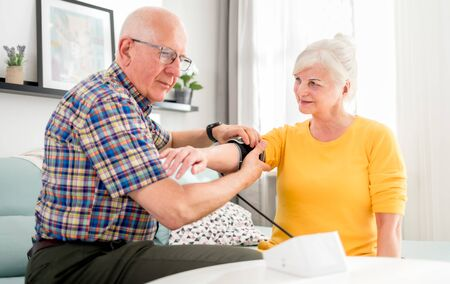 Senior husband doing blood pressure measurement to his wife at home