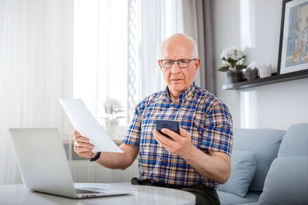 Worried senior male checking bills using laptop at home Reklamní fotografie - 127359214