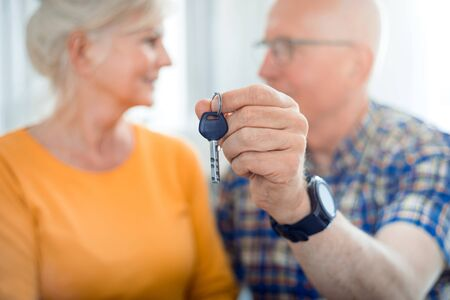 Happy senior couple with keys for new house Reklamní fotografie - 127359281