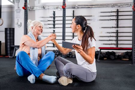 Trainer giving highfive to senior woman at the gym after workout Reklamní fotografie - 127359282