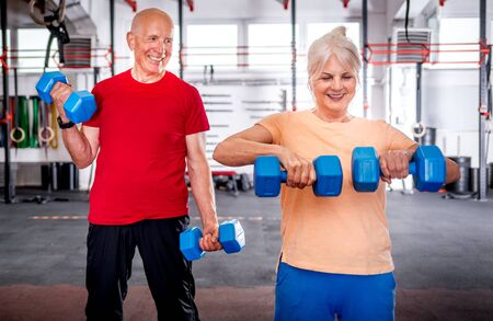 Senior people with dumbbells doing exercises at the gym Reklamní fotografie