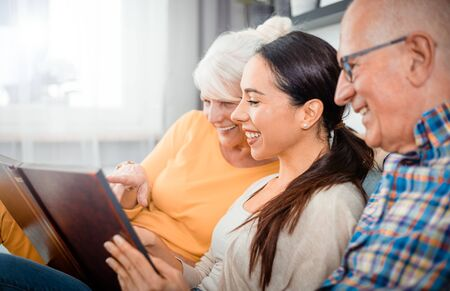 Happy senior parents with their daughter looking at photos in family album Reklamní fotografie - 127359341