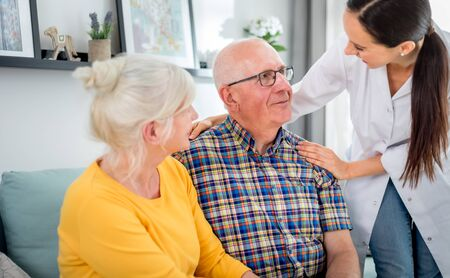 Smiling nurse talking with senior couple during home visit Banque d'images