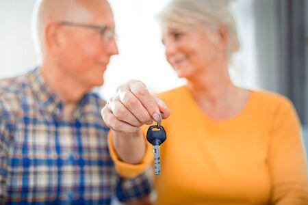 Happy senior couple with keys for new house Reklamní fotografie - 127359355