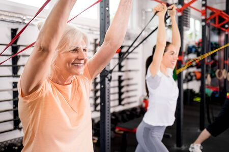 Senior people with trainer using resistance band doing exercises at the gym Reklamní fotografie - 127359358