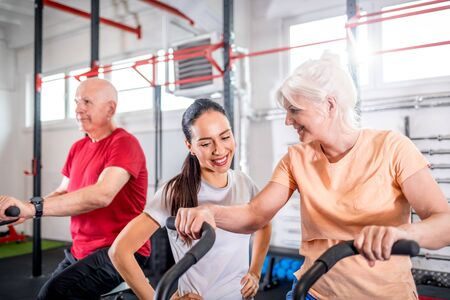 Senior couple biking at the gym with personal trainer Reklamní fotografie - 127359359