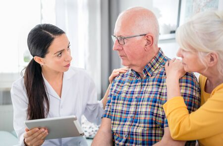 Nurse gives bad news to worried senior couple at home Reklamní fotografie - 127359364