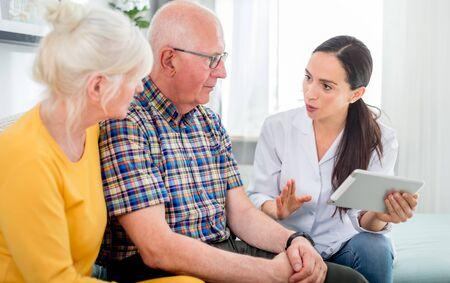 Nurse gives treatment advices to senior couple at home Reklamní fotografie - 127359365