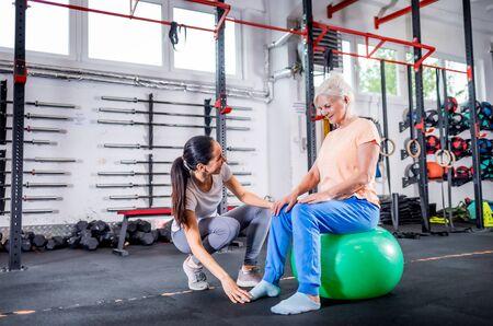 Senior woman with trainer doing rehab using pilates ball in the rehabilitation center Reklamní fotografie - 127359367
