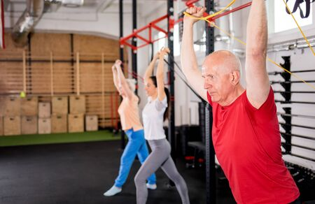 Senior people with trainer using resistance band doing exercises at the gym