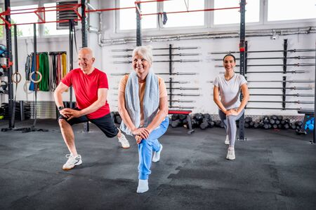 Personal trainer with senior couple doing rehab exercises at the gym Reklamní fotografie - 127359452