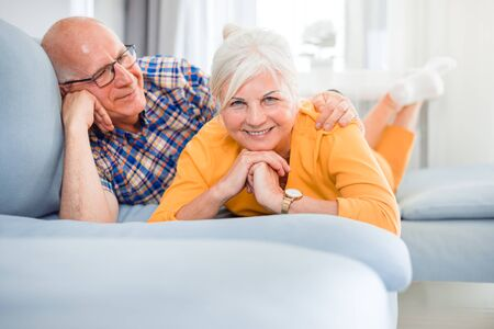 Portrait of cheerful senior couple relaxing and lying on sofa at home Reklamní fotografie - 127359453
