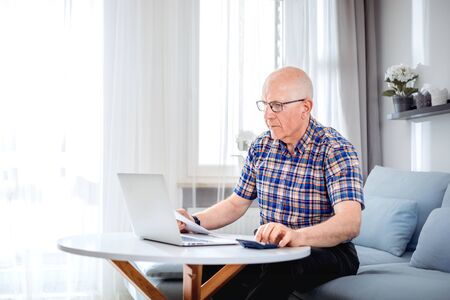 Senior male calculating bills using laptop at home Reklamní fotografie - 127359455