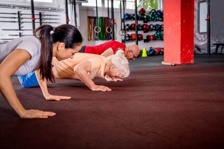 Senior people workout with personal trainer at the gym Reklamní fotografie