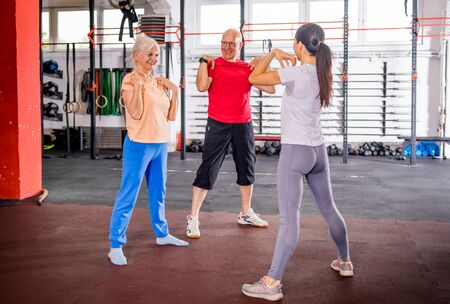 Senior people workout with personal trainer in rehabilitation center Reklamní fotografie - 127359459