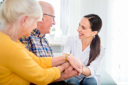 Smiling nurse talking with senior couple during home visit Reklamní fotografie - 127359461