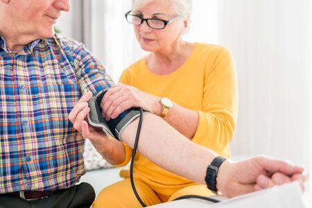 Senior wife doing blood pressure measurement at home to her husband Reklamní fotografie - 127359465