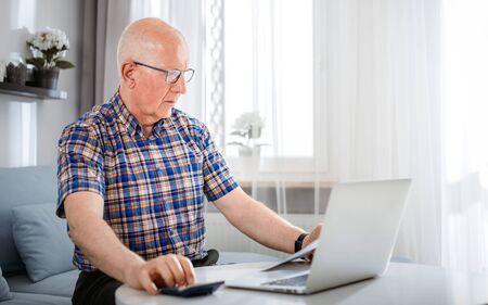 Senior male calculating bills using laptop at home Reklamní fotografie - 127359471