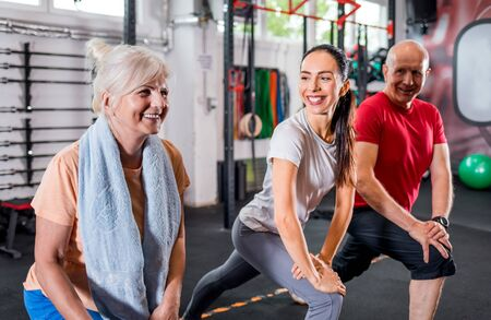 Personal trainer with senior couple doing rehab exercises at the gym Reklamní fotografie - 127359473