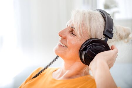 Relaxed senior woman listening her favourite music at home using big headphones Reklamní fotografie - 127359475