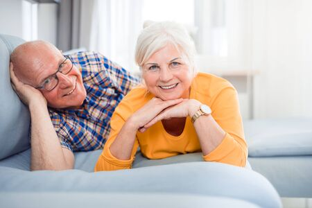 Portrait of cheerful senior couple relaxing and lying on sofa at home Reklamní fotografie - 127359503