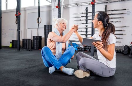 Trainer giving highfive to senior woman at the gym after workout Reklamní fotografie - 127359506