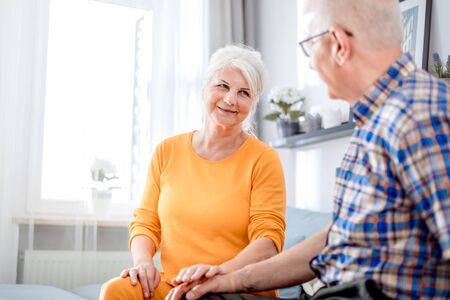 Senior couple caress and comfort each other holding hands at home