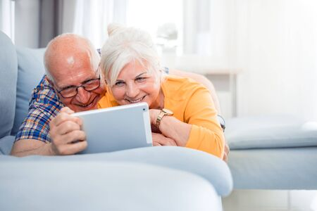 Happy senior couple video chatting using tablet at home Reklamní fotografie - 127359515